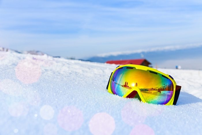 View of yellow ski mask with reflection of mountain on white icy snow.